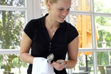Kellnerin deckt Besteck ein